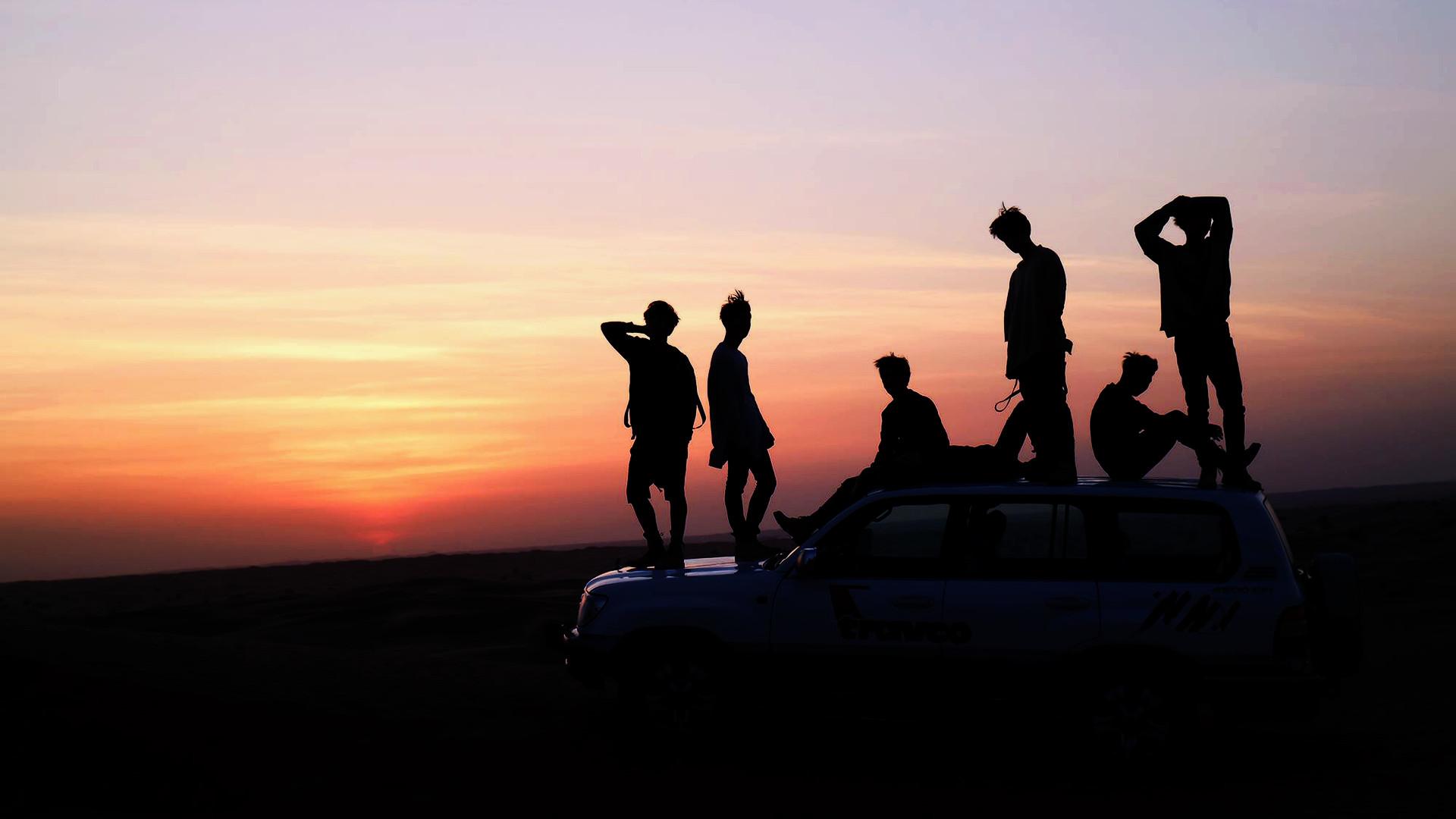 Wallpaper BTS đứng dưới ánh hoàng hôn trên một chiếc xe